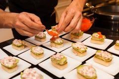 厨师准备了在白色板材的可口食家canapé起始者 库存图片