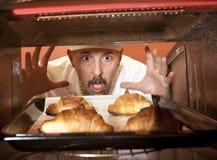 厨师准备在烤箱的新月形面包 免版税库存照片