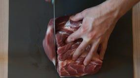 厨师切与刀子的生肉 切猪肉的厨师 开始剪切肉 股票录像