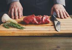 厨师切口在木板的小腓厉牛排在餐馆厨房 库存照片