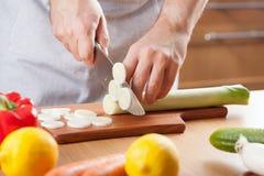 厨师切口韭葱在厨房里 免版税库存图片