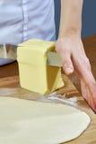 厨师切在面团准备乳酪蛋糕系列充分的烹调食物食谱传播的黄油一个大片断 免版税库存图片