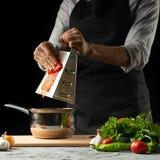 厨师切并且品尝蕃茄,意大利西红柿酱为通心面做准备 薄饼 意大利烹调食谱的概念 免版税库存图片