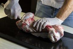 厨师切开一根小牛肉骨头 库存照片