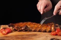 厨师切开它与快刀立即可食的猪排,说谎在一张老木桌上 一个人准备一顿快餐对啤酒 免版税库存图片