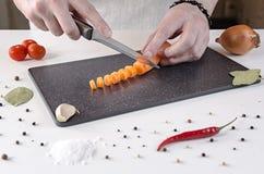 厨师切红萝卜成在一个黑切板的小切片 免版税库存照片