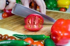厨师切蕃茄成在一个切板的片断有一把锋利的烹调刀子的 免版税库存照片