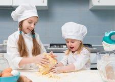 厨师制服的两个小女孩揉面团 免版税库存图片