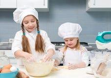 厨师制服的两个小女孩揉面团 库存照片