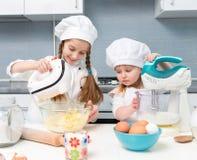 厨师制服的两个小女孩有在桌上的成份的 库存图片
