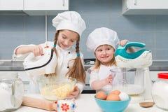 厨师制服的两个小女孩有在桌上的成份的 免版税库存图片