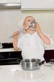 厨师制服的小男孩舔杓子的 图库摄影