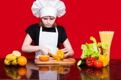 厨师制服的愉快的小女孩在厨房里切果子 图库摄影