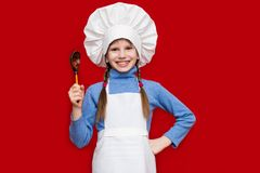 厨师制服的愉快的小女孩拿着匙子 库存图片