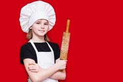 厨师制服的愉快的小女孩拿着滚针 免版税图库摄影