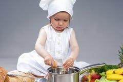 厨师制服的白种人小女孩用新鲜的鸡蛋 库存图片
