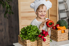 厨师制服的英俊的小孩有菜的 在家烹调在厨房里 素食主义者 健康的食物 免版税图库摄影