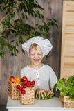 厨师制服的英俊的小孩有菜的 在家烹调在厨房里 素食主义者 健康的食物 库存照片