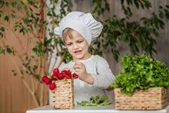 厨师制服的英俊的小孩有菜的 在家烹调在厨房里 素食主义者 健康的食物 免版税库存照片
