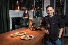 厨师厨师举行杯在餐馆酒吧的红葡萄酒 免版税库存照片