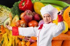 厨师厨师拿着一把刀子反对新鲜蔬菜背景 库存照片
