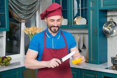 厨师去的被切的黄色喇叭花胡椒 烹调菜的厨师人在厨房里 切橙色辣椒粉的人开始 图库摄影