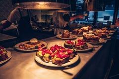 厨师和厨师在餐馆准备了命令鳄梨调味酱捣碎的鳄梨酱鲕梨多士和新鲜的薄煎饼用果子在命令柜台 免版税库存照片