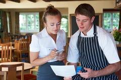 厨师和女服务员谈论菜单在餐馆 免版税库存照片