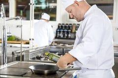 厨师在一个专业厨房倾吐在平底锅的橄榄油 免版税库存照片