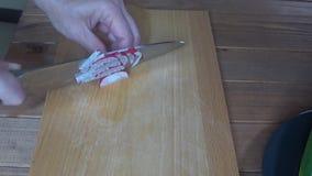 厨师在一个切板的切片萝卜,接近剁萝卜 股票视频