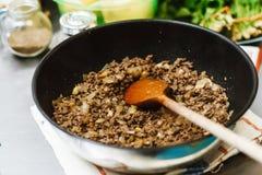 厨师在一个深平底锅烤剁碎 准备好充塞用在一个碗的葱在香料和绿色背景  库存照片