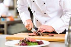 厨师在准备食物的餐馆厨房里 免版税库存图片