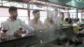 厨师在客户的白色制服烹调在酒吧桌上在餐馆的开放厨房 股票视频