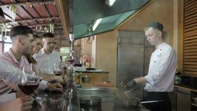 厨师在客户的白色制服烹调在酒吧桌上在餐馆的开放厨房 影视素材