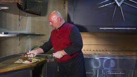 厨师在板材上把准备着的肉放 股票录像