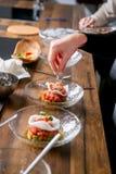 厨师在板材上把鞑靼的金枪鱼放 主要类在厨房里 烹调的过程 逐步 指导 特写镜头 库存图片