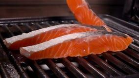 厨师在格栅花格上把未加工的三文鱼内圆角放 股票视频