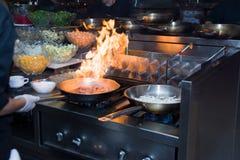 厨师在火炉的餐馆厨房里与平底锅,做在食物的flambe 低ligth选择聚焦 免版税库存图片