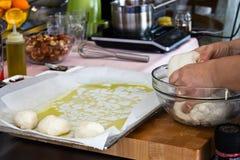 厨师在烘烤准备从发酵面团的小圆面包并且传播 免版税库存图片