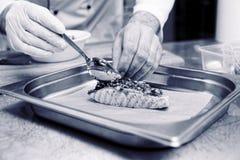 厨师在烤三文鱼上把草本调味汁放,被定调子 库存照片