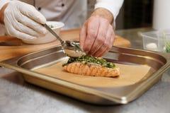 厨师在烤三文鱼上把草本调味汁放 免版税库存图片
