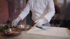 厨师在烤箱倾倒在说谎在平板炉的鱼和菜之上一个可口盘的olei并且投入它 股票视频