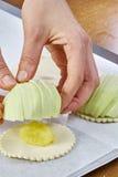 厨师在面团充分的膳食食谱乳酪蛋糕上把苹果放 库存照片