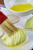 厨师在面团充分的膳食食谱乳酪蛋糕上把苹果放 库存图片