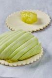 厨师在面团充分的膳食食谱乳酪蛋糕上把苹果放 图库摄影
