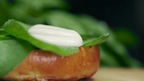 厨师增加奶油沙司到与菜的汉堡和绿色,小圆面包和汉堡,做汉堡,烹调快速 影视素材