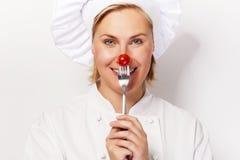 厨师妇女holdinh一把叉子用反对她的鼻子的蕃茄,站立 免版税图库摄影