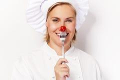 厨师妇女holdinh一把叉子用反对她的鼻子的蕃茄,站立 免版税库存图片