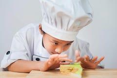 厨师孩子,女孩穿戴厨师服装 免版税图库摄影