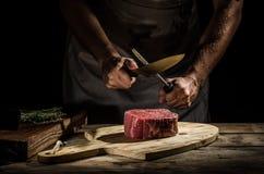 厨师屠户准备牛排 免版税库存照片